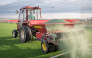 a picture of a tractor spreading turf infill.