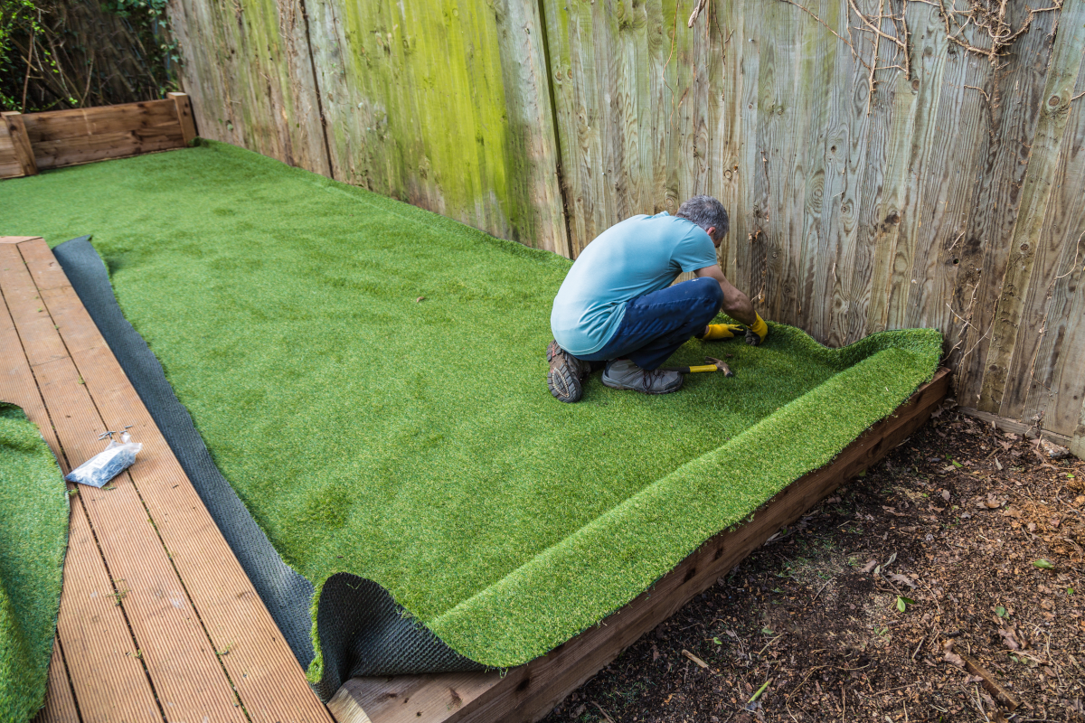 a picture of a person installing artificial turf